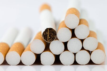 Closeup of many cigarettes The cigarette end is brown and the tip is white. Arranged in a triangle On a white background Banque d'images
