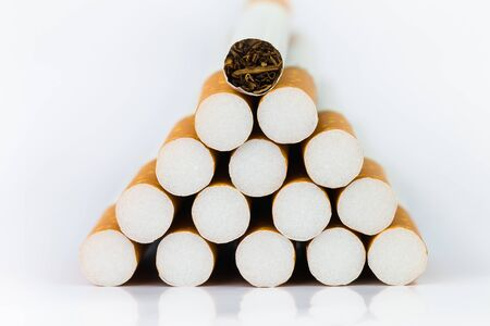 Closeup of many cigarettes The cigarette end is brown and the tip is white. Arranged in a triangle On a white background 版權商用圖片