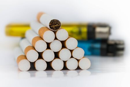 Closeup of many cigarettes The cigarette end is brown and the tip is white. Arranged in a triangle And with a blue match placed behind On a white background On a white background