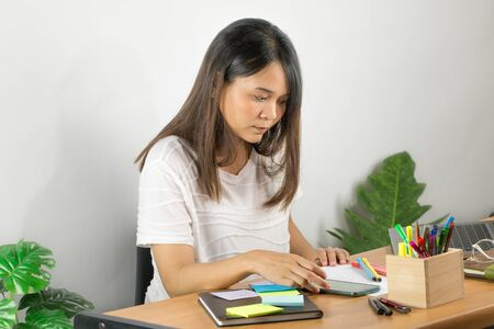 Asian woman wearing a white T-shirt I'm working seriously at home. Open the grey notebook screen on the brown wooden desk and the white wall background and decorate with green trees.