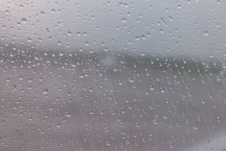 The raindrops are attached to the clear glass in front of the car. When it rains During the day time, the picture is partially clear.