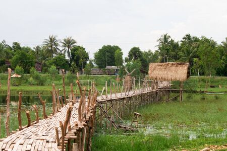 A wooden hut in the middle of the water and a wooden pathway connecting to the resting spot Thatched roof According to the way of life of people living in southern Thailand