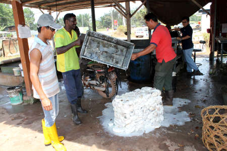 put together: Rubber workers put down rubber for merchandise Editorial