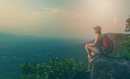 young asian woman hiker enjoy the view on mountain peak cliff Stock Photo