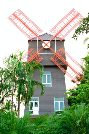 aero generator: Windmill tower behind garden at a gas station in Thailand