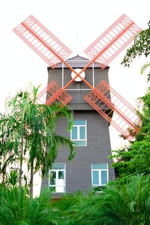 aero generator: Windmill tower behind garden at a gas station in Thailand