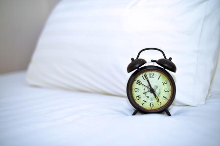 arredamento classico: Retro alarm clock on bed and white pillow Archivio Fotografico