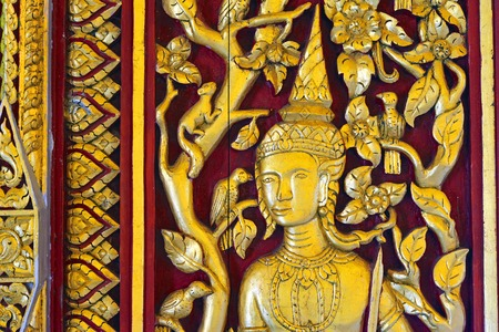 wood carving door: Buddhism wood carving on temple entrance door, native Thai style Stock Photo