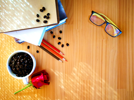 Coffee bean on cup, rose, glass and books on wood table of background concept