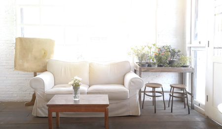 White sofa seat near windows. It is a decoration in living room