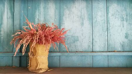 Dry rice in sack put decorate coffee shop.Background is Thailand pattern wood wall in blue color