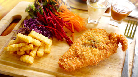 Fish steak.French fries and  Vegetable salad on wood dish. breakfast  food table