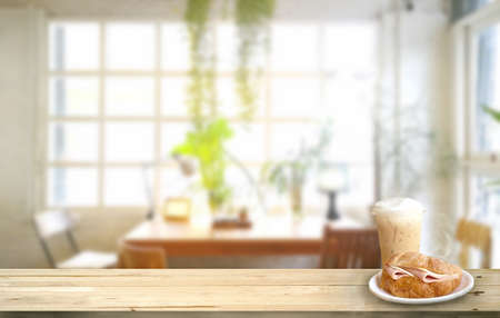 Mock up Croissant ham and Ice cappuccino on wood table .Background blur indoor cafe and restaurant Stock fotó