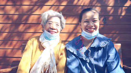 Pet Cha boon ,Thailand , Two  woman smiling brightly In the midst of the coronavirus(covid-19). they were wearing face masks. When they going out Sajtókép