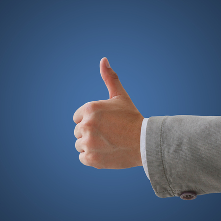 Closeup of male hand showing thumbs up sign against Stock Photo