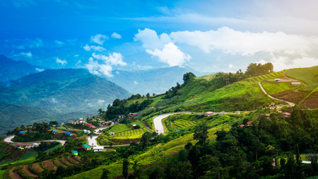 switchback: Switchback and village on mountain with blue sky landscape Stock Photo