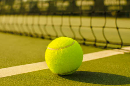 to play ball: Tennis Ball on the Court with the Net in the background Stock Photo