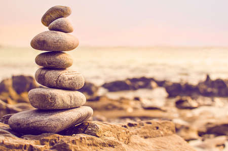sustained: Stones laid out in the form of a pyramid on the seashore Stock Photo