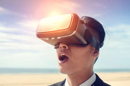 Businessman wearing virtual reality glasses . Mixed media