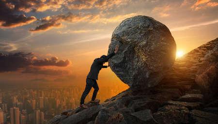 Homme d'affaires poussant la grosse pierre jusqu'à la colline, affaires lourdes tâches et concept de problèmes.