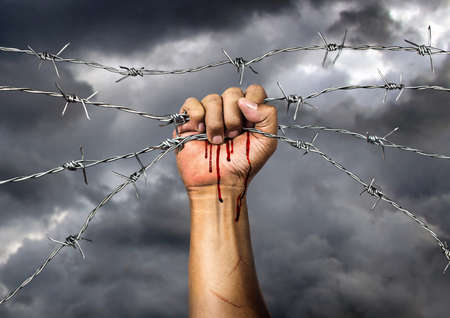 Hand holding a barbed wire on black background , The concept of malice