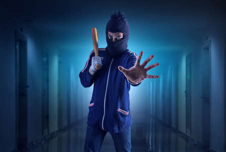 Criminal or bandit holding a baseball bat.