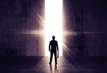 Businessman looking out of abstract opening in wall with bright daylight in concrete interior. Concept for success.
