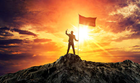 Businessman with flag on mountain top. Concept for success. 版權商用圖片