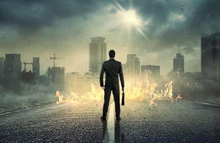 Businessman standing with back and looking at sunrise above city. Concept for success.