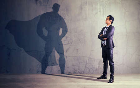 Asian businessman with his shadow of super hero on the wall. Concept of powerful man 版權商用圖片