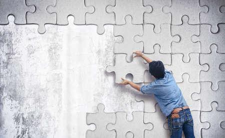 Homme faisant un puzzle sur le mur. mur vide avec un espace pour le texte Banque d'images