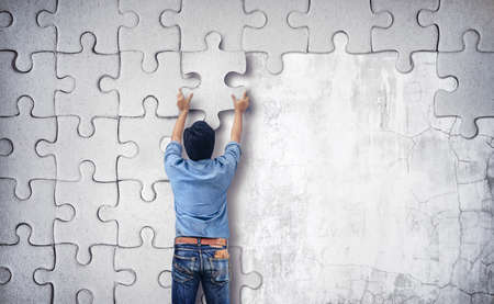 Man making a puzzle on the wall.  empty wall with space for text