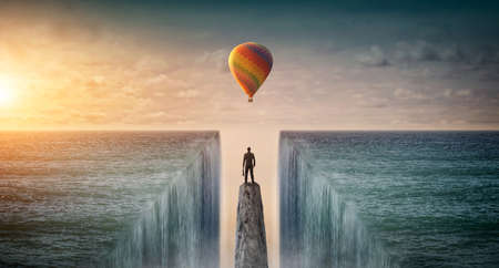 Businessman standing on edge of rock mountain and looking at Balloon. Concept for success 版權商用圖片