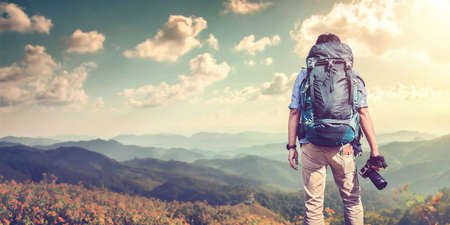 A young guy with a backpack traveler standing on a cliff holding camera and watching White misty mountains. Travel photo lifestyle Imagens