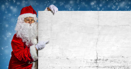 Happy santa claus pointing on blank advertisement banner with copy space. Christmas theme, sales - Image