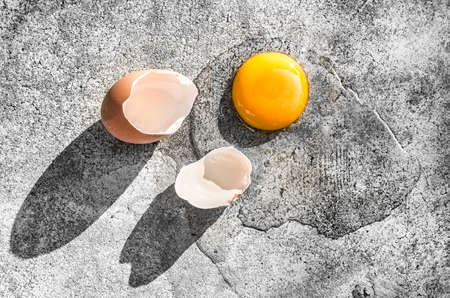 Raw egg with eggshells on the ground.