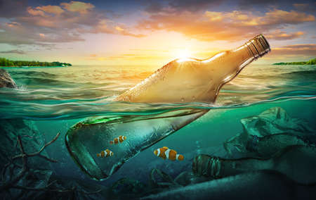 Small fishes in a bottle among ocean pollution. Environment concept Imagens
