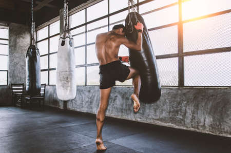 Muay thai fighter training in the gym with the punch bag Imagens