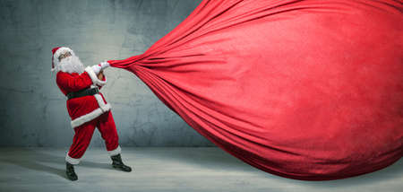 Santa Claus with big bag on blank advertisement banner with copy space. Christmas theme, sales - Image