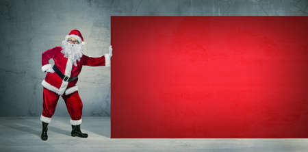 Santa Claus holding on blank advertisement banner with copy space. Christmas theme, sales - Image