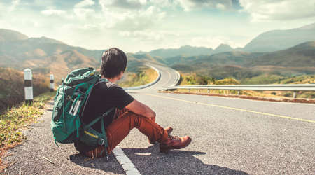Young man sitting on the roadside. Backpackers, Travel and Holiday concepts.
