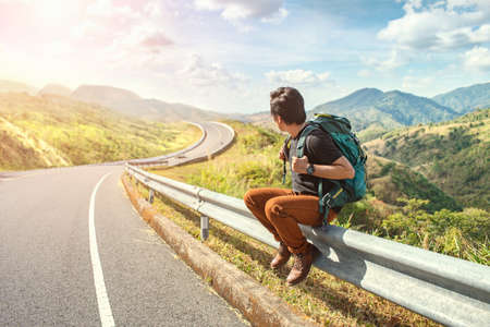 Young man sitting on the roadside. Travel and Holiday concepts. Backpacker on road. Travel man hitchhiking