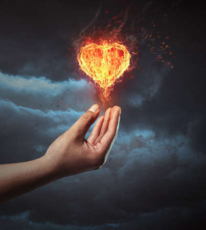 Hand holding fire heart. Symbolize giving love concept.