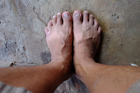 dirty feet: Dirty feet on the cement floor.