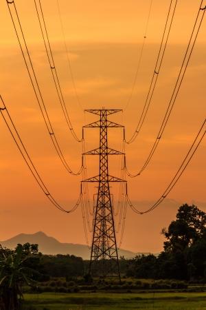 Siluetas de las líneas de energía en un paisaje plano y la puesta de sol