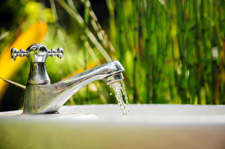 grifo agua: Gota del agua de grifo y el fondo de la naturaleza Foto de archivo