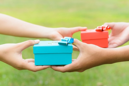 woman and man give a gifts, on green  Standard-Bild