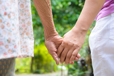 2 people: Senior and young holding hands Stock Photo