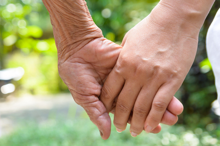Senior and young holding hands Standard-Bild