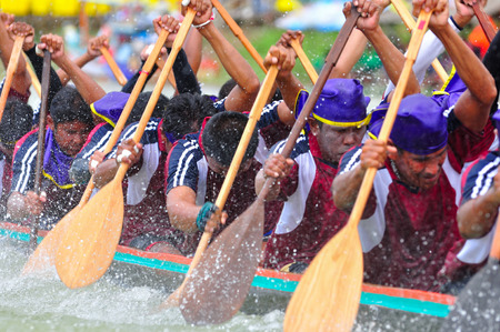 CHUMPHON, THAILAND-OCT 21  Unidentified rowers in Climbing Bows toward Snatching a Flag native Thai long boats compete during King s cup Native Long Boat Race Championship on Oct 21, 2013 in Chumphon, Thailand